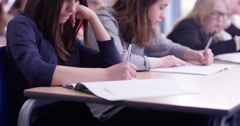 4k, A young girl in a classroom concentrating on her test - stock footage