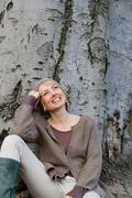 Woman leaning at tree laughing Stock Photos