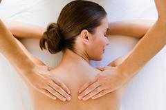 Hands massaging woman's shoulders - stock photo