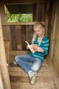 Young girl reading in treehouse - stock photo