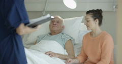 4K Daughter visiting elderly father in hospital & medical worker talking to them Stock Footage