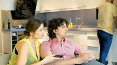Couple watching television while their friend cooking dinner Stock Footage