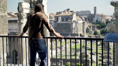Young man looking at ruins of the famous Forum Romanum in Rome Stock Footage