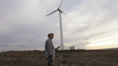 Engineer and windmill at sunset Stock Footage