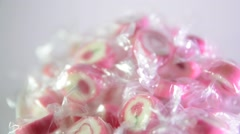 Bright pink candy in a transparent wrapper on a light background rotate slowly. Stock Footage