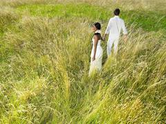 Married couple walking in a field Stock Photos