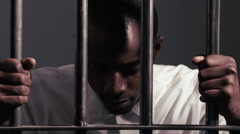 A desperate man holding the bars to his prison cell Stock Footage