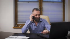 Businessman at the age of a lot of fun talking with a friend on the phone - stock footage