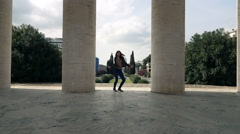 Happy woman jumping and dancing between columns, super slow motion Stock Footage