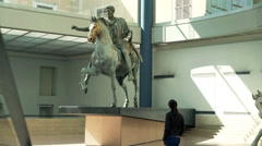 Woman looking at roman equestrian statue of Marcus Aurelius at Museum Stock Footage