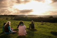 Children watching sunset on hill - stock photo