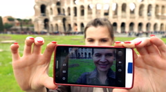 Tourist taking photo with cellphone standing close to the Colloseum slow motion Stock Footage