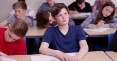 4k, School boy day dreaming beside his classmate in classroom - stock footage
