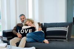 Man and woman on sofa with cushion Stock Photos