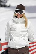 Female snowboarder walking with her snow - stock photo