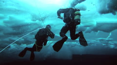 Two divers swimming under the ice of North Pole. - stock footage
