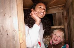 Two young girls at treehouse door Stock Photos