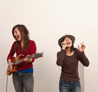 Two women singing and playing guitar Stock Photos