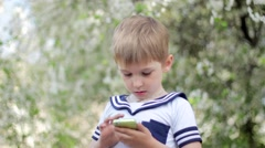 Young little boy plays games on smartphone. Spring park - stock footage