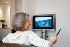 Mature woman watching television Kuvituskuvat