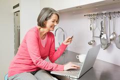 Mature woman using internet banking - stock photo