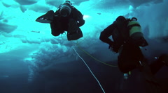 Divers dive under the ice of the North Pole in the Arctic. Stock Footage