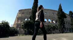 Young woman walking close to the Colloseum in Rome, super slow motion Stock Footage