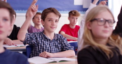 4k, School children raising their hands ready to answer the question Stock Footage
