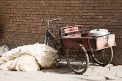 Bicycle next to pile of wool on footpath - stock photo