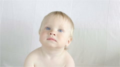 Adorable little baby is looking into the camera Stock Footage
