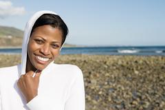 Smiling woman on a shingle beach Stock Photos
