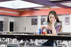 Girl alone at lunch Stock Photos