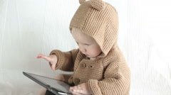 A cute little baby boy watching a movie on an tablet Stock Footage