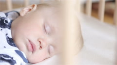 Peaceful adorable baby sleeping on his bed in a room. Stock Footage