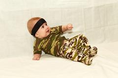 The baby in camouflage clothes on a white background Stock Photos
