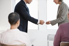 Businesspeople exchanging business cards - stock photo