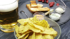 A glass with beer and snacks on a plate on a dark table. Stock Footage