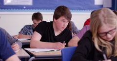 4k, A male student using the internet during an exam gets caught by a teacher. Stock Footage
