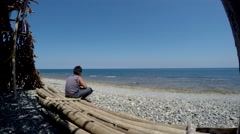 Fat boy gazing  at wide open sea sitting - stock footage