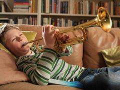 Boy, 11 playing trumpet Stock Photos