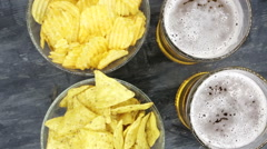 A glass with beer and snacks on a plate on a dark table Stock Footage