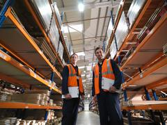 Workers In Aisle Of Warehouse Stock Photos