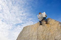 Climber looking at map Stock Photos