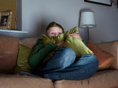 Boy, 11 watching scary movie Stock Photos