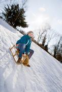 Girl riding a sledge in snow Stock Photos