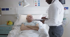 4K Friendly doctor talking to elderly patient at his bedside Stock Footage
