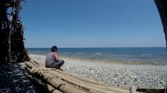Fat boy gazing  at wide open sea sitting Stock Footage
