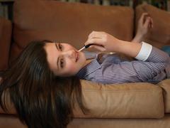 Girl, 14 applying lip gloss - stock photo