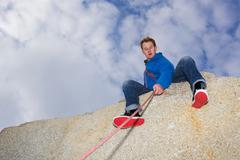 climber belaying on snow covered peak - stock photo