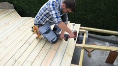 Carpenter building wooden deck Stock Footage
